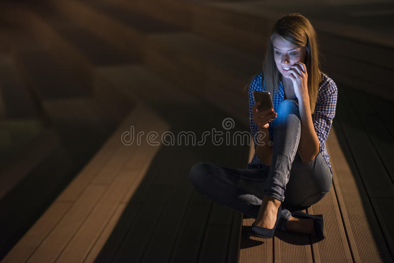 Excited beautiful girl receiving a sms message with good news in a mobile phone outside royalty free stock image
