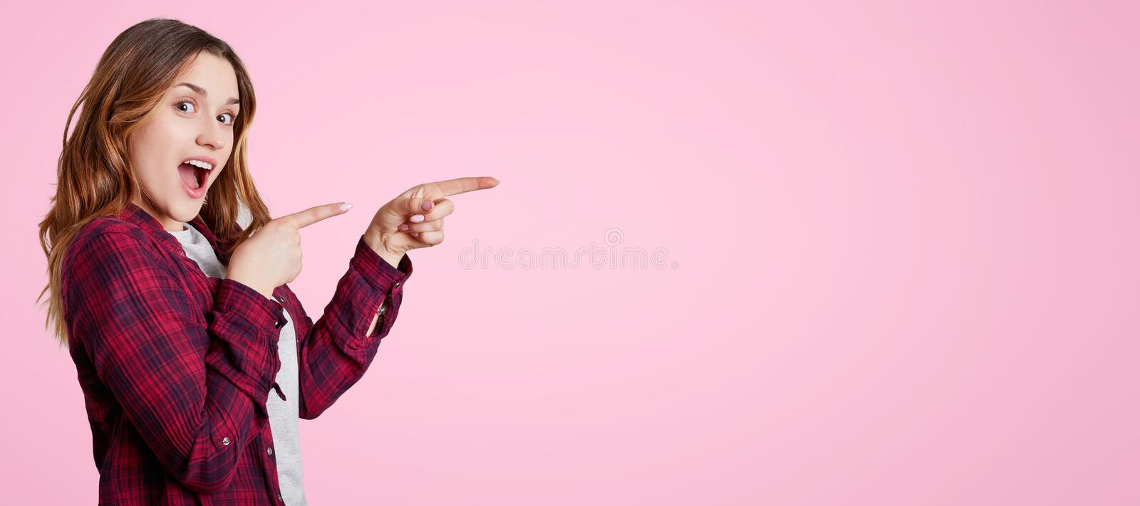 Excited beautiful woman stands sideways, wears chemise, points with fore fingers aside at blank copy space for your advertisment o. R promotional text. Joyful royalty free stock photos