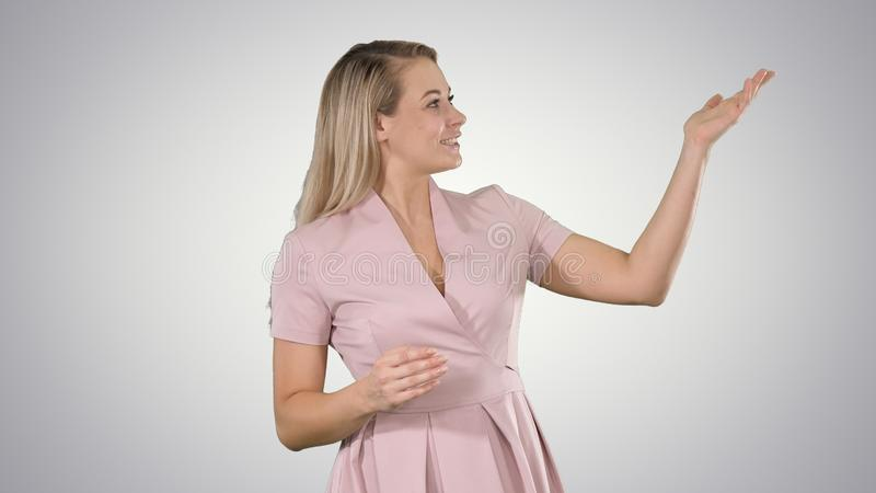 Excited beautiful young woman in pink dress talking to camera on gradient background. Medium shot. Excited beautiful young woman in pink dress talking to camera royalty free stock images