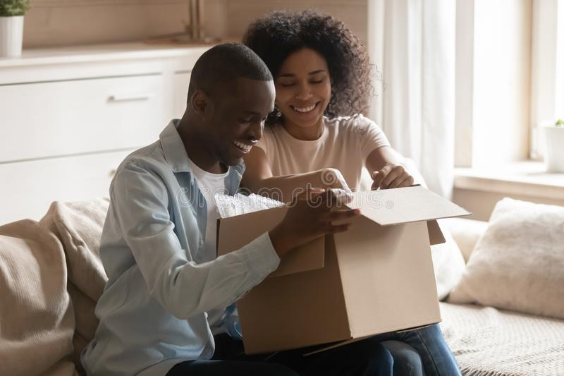 Excited biracial client couple unpack delivery box. Excited african American buyer couple sit on couch at home unpacking cardboard box from delivery service royalty free stock image
