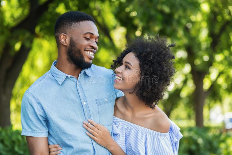 Excited black couple bonding while walking in park royalty free stock images
