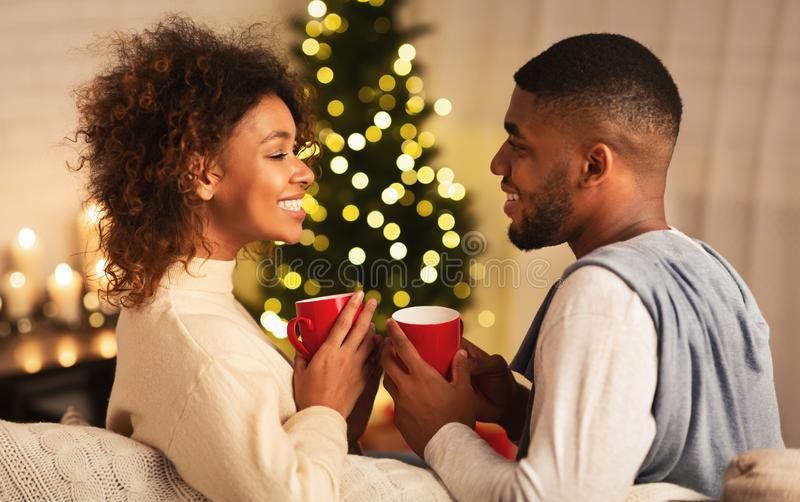 Excited black couple drinking coffee on Christmas eve stock images