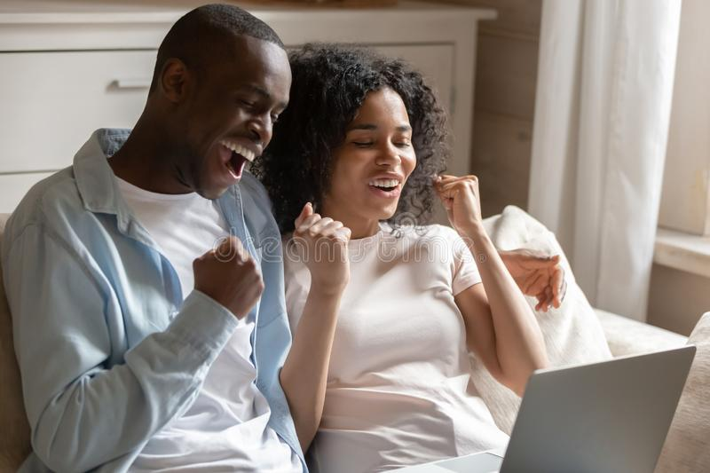 African spouses look at laptop scream with joy celebrate victory stock photos