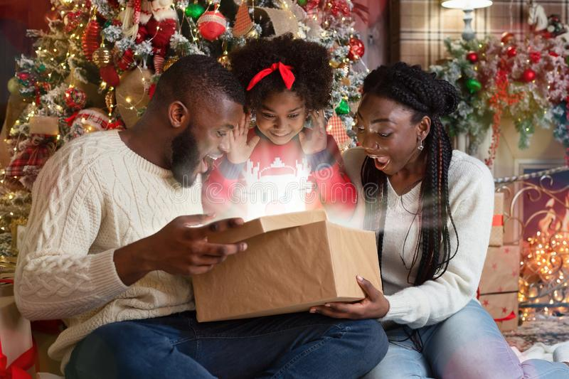 Excited black family of three opening shining Christmas gift box stock image