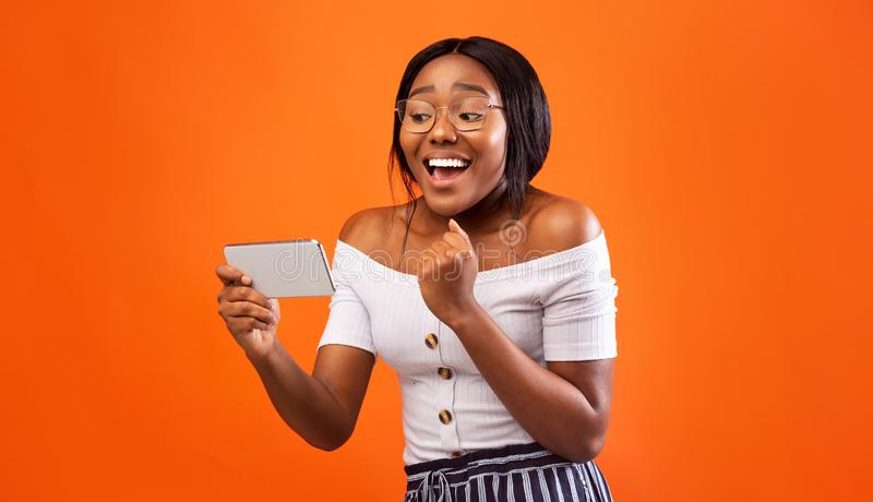 Excited Black Girl Holding Smartphone Gesturing Yes, Studio Shot. Excited Black Girl Holding Smartphone Gesturing Yes Standing Over Orange Background. Studio royalty free stock photos