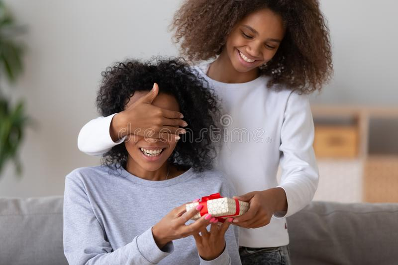 Excited black girl make birthday surprise for mom. Excited African American daughter close mom eyes, making birthday surprise, happy black teenage girl give stock photo