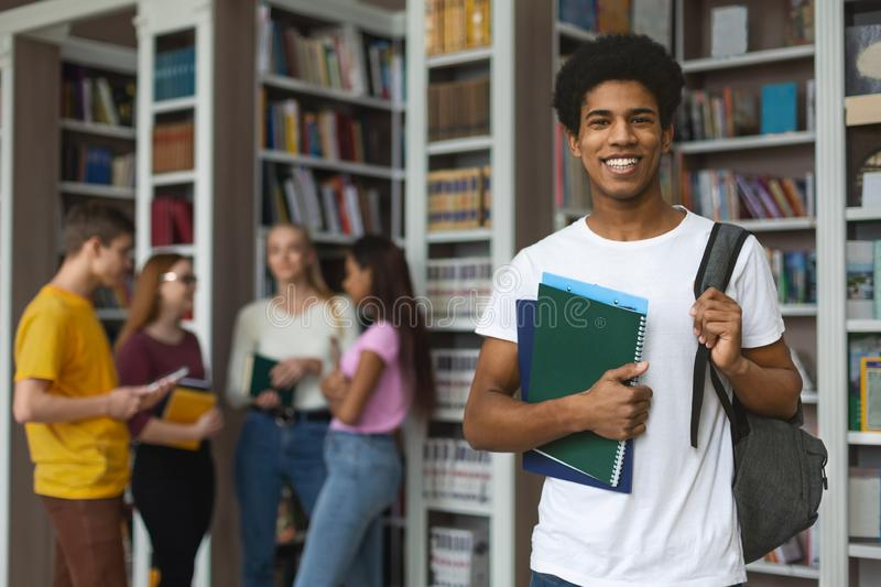 Excited african american student posing next to bookshelves in library. Excited black guy ready for studying, posing next to bookshelves in campus library, empty royalty free stock images