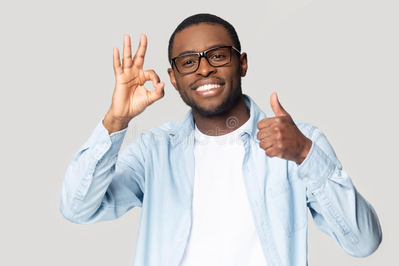Excited black male in glasses recommend service or offer. Happy african American male in glasses look at camera show thumb up all right sign satisfied with stock photos