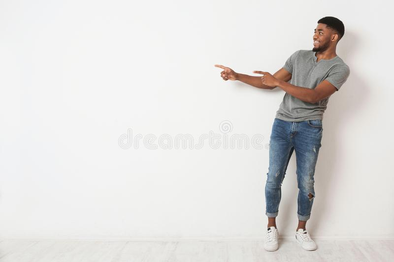 Excited black man pointing two fingers aside at copy space royalty free stock image