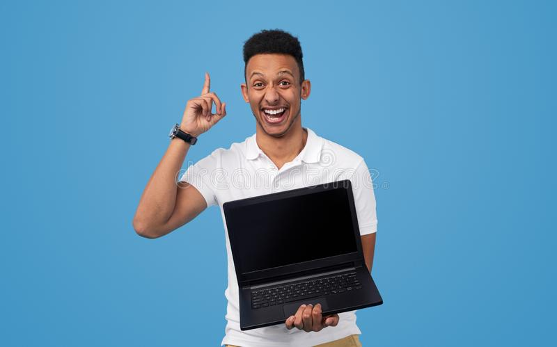 Excited black man presenting good deal on laptop. Handsome African American male cheerfully smiling and showing laptop with empty screen while advertising sale stock photo