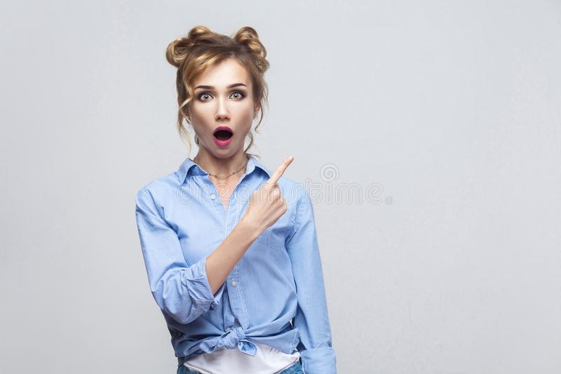 Excited blonde woman pointing finger sideways, raising eyebrows stock photos