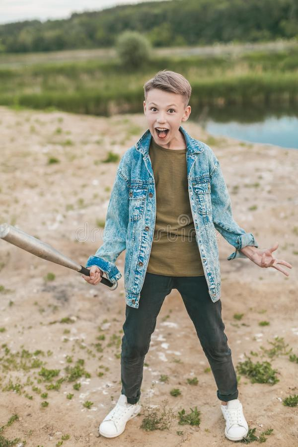 Excited boy in denim jacket holding baseball bat and looking. At camera outdoors royalty free stock image