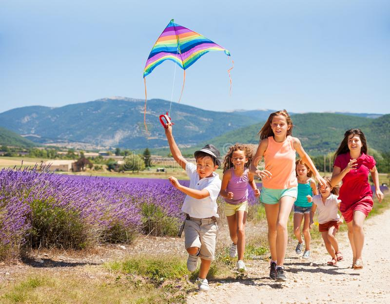 Excited boy flying rainbow kite with his friends stock photos