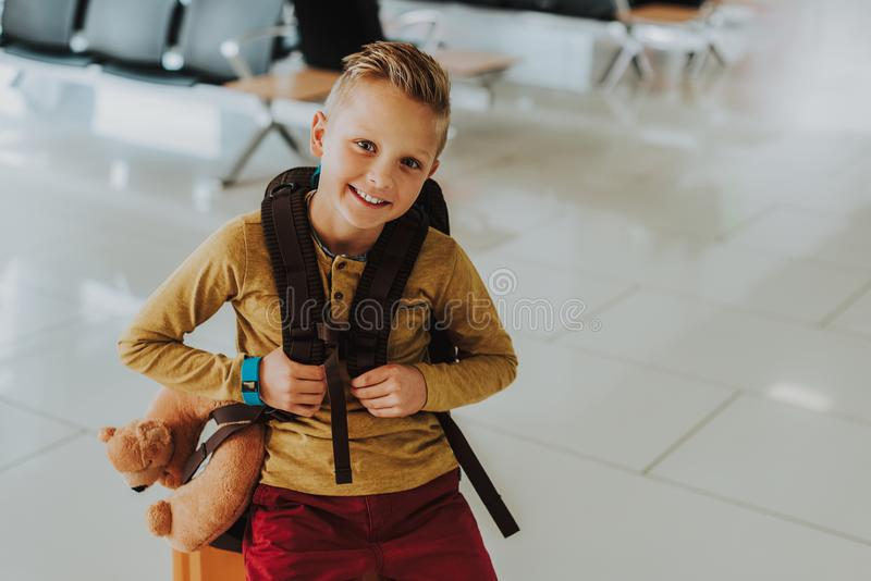 Excited boy is going on tour with smile. Top view waist up portrait of delighted boy sitting on suitcase. He is carrying backpack and teddy bear pillow while royalty free stock photo