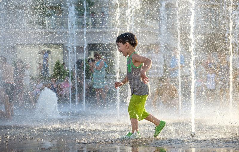Excited boy having fun between water jets, in fountain. Summer i stock images