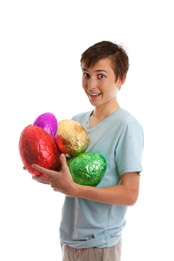 Excited boy holding chocolate easter eggs. An excited boy holds variety of colourful foil wrapped chocolate easter eggs royalty free stock photos