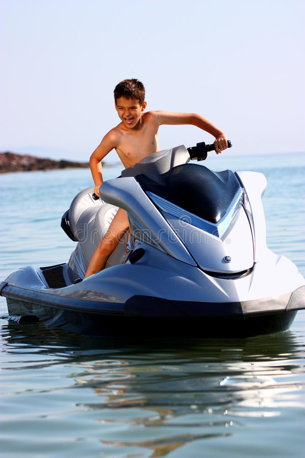Excited boy on jet ski. A happy excited kid on a jet ski royalty free stock photography