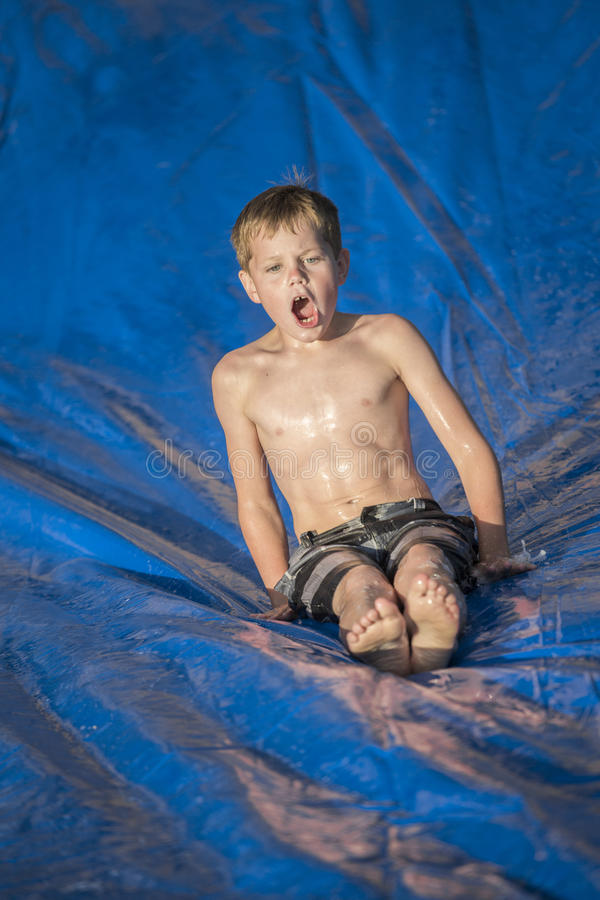 Excited boy playing on a slip and slip outdoors stock photography