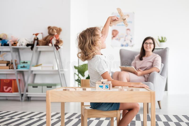 Excited boy playing with a toy plane in a therapist`s office. Concept stock photos