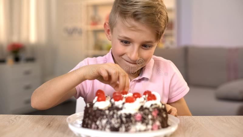 Excited boy taking cherry from top of delicious chocolate cake, birthday party royalty free stock image