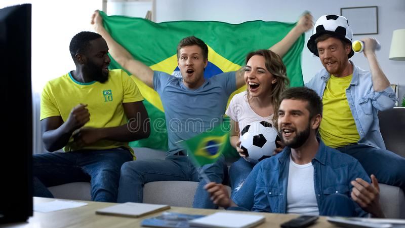 Excited Brazilian friends cheering for national team, celebrating winning goal stock images