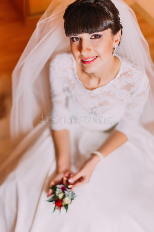 Excited bride in gorgeous white dress waiting for her wedding posing with cute floral boutonniere royalty free stock photography
