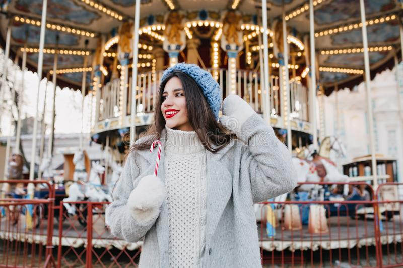 Excited brunette girl in blur knitted hat waiting for friend in amusement park in winter day. Outdoor photo of happy stock photography