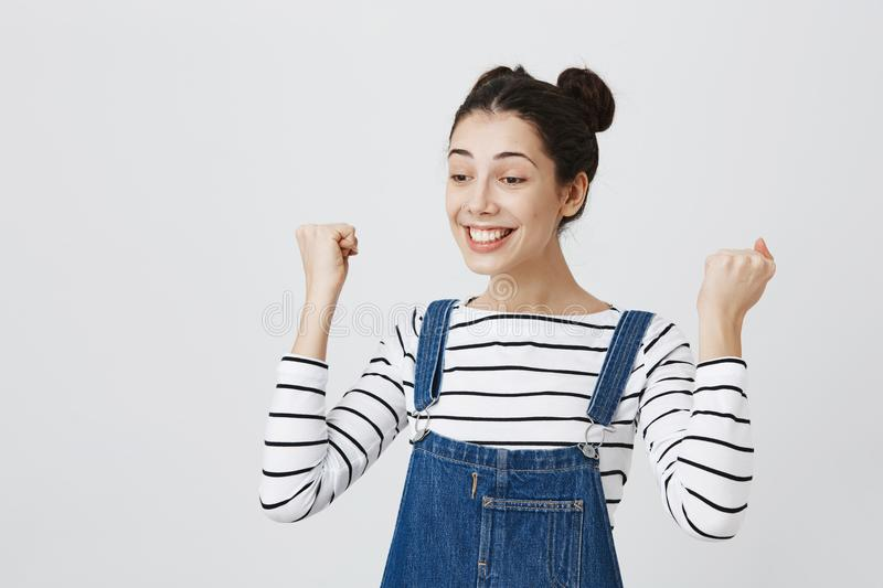 Excited brunette girl with hairbuns in striped top and denim clothes glad to achieve sucess, clenches fists and smiling stock image