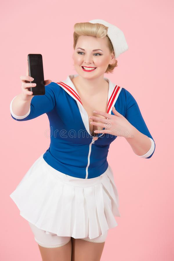 Excited bug eyed young blonde female wearing sailor shirt and headband with smiling face emotion pointing at cell phone. royalty free stock photography