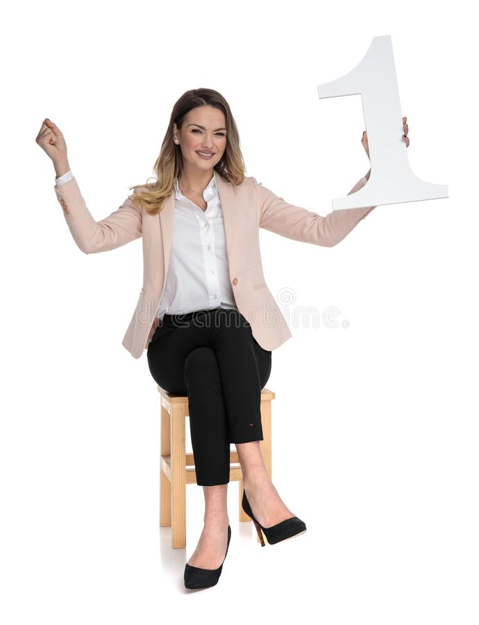 Excited busiensswoman holds number one in her hand and celebrates. Excited businesswoman holds number one in her hand and celebrates while sitting on wooden royalty free stock images