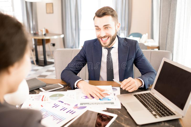 Excited business analyst working with colleague in cafe. Cheerful excited bearded young businessman in formal suit laughing while discussing statistics with royalty free stock photos