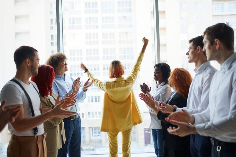 Excited business group of young people at the office with arms up royalty free stock image