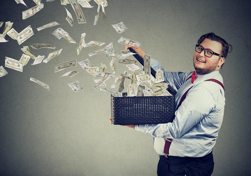 Excited business man opening a box letting dollar banknotes to fly away. Excited business man in glasses opening a box letting dollar banknotes to fly away stock image