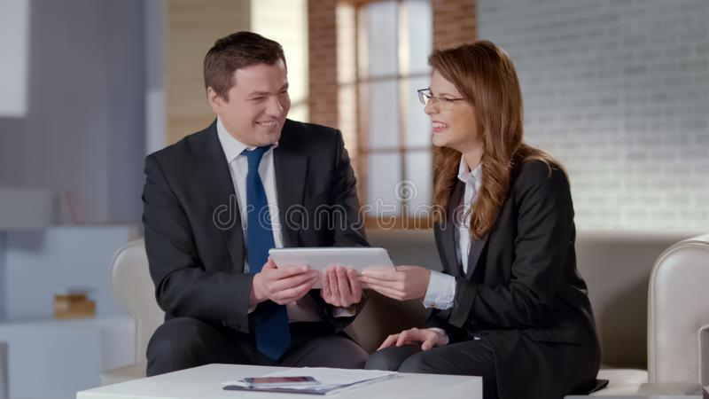 Excited business partners laughing, holding tablet with online startup project stock photos