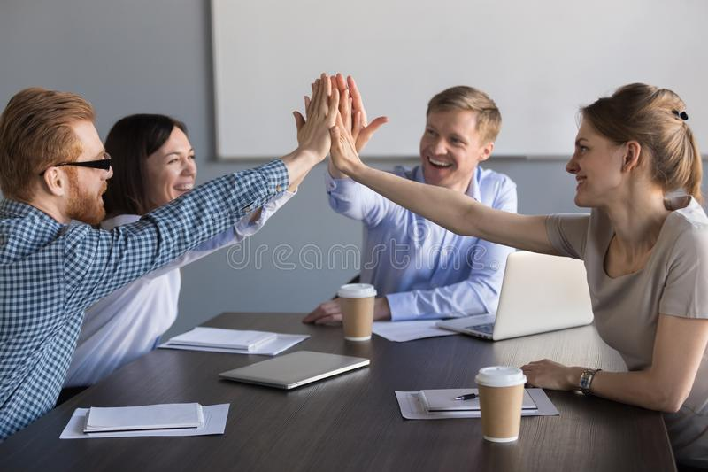 Excited business team of employees giving high five during meeti. Excited happy business team of employees or partners group giving high five during meeting royalty free stock photo