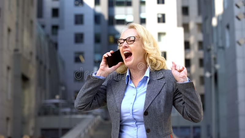 Excited business woman celebrating success talking phone outdoor, work promotion stock photo
