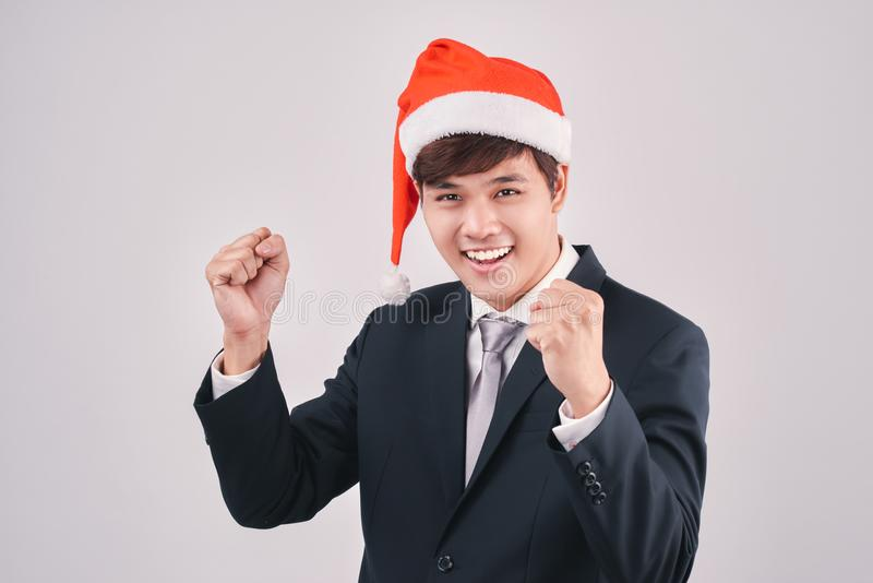 Excited businessman in black suit and santa hat isoalted on whit stock photography