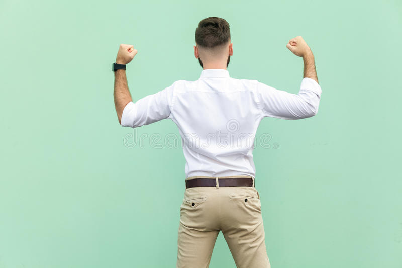 Excited businessman celebrates a career achievement. Back view of a young adult businessman, on light green background. stock photography