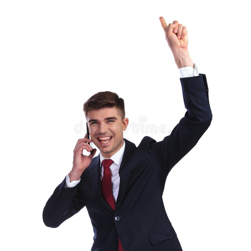 Excited businessman speaking on the phone is celebrating royalty free stock image