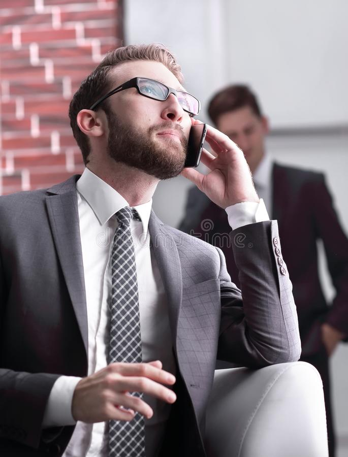 Handsome businessman speaking on mobile phone in office. Excited businessman talking on the mobile phone while is watching royalty free stock photos
