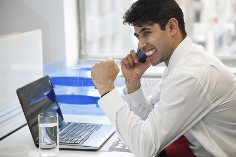 Excited businessman using cell phone at office desk royalty free stock image