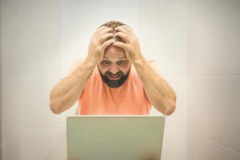 Excited businessman working on laptop and talking on phone seated on the toilet stock photo