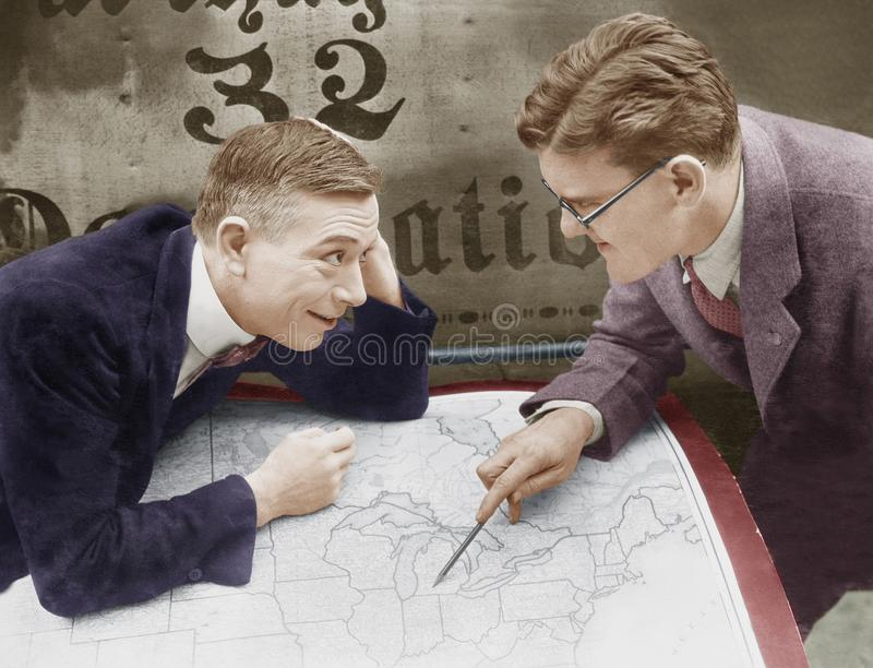 Excited businessmen meeting with map stock image