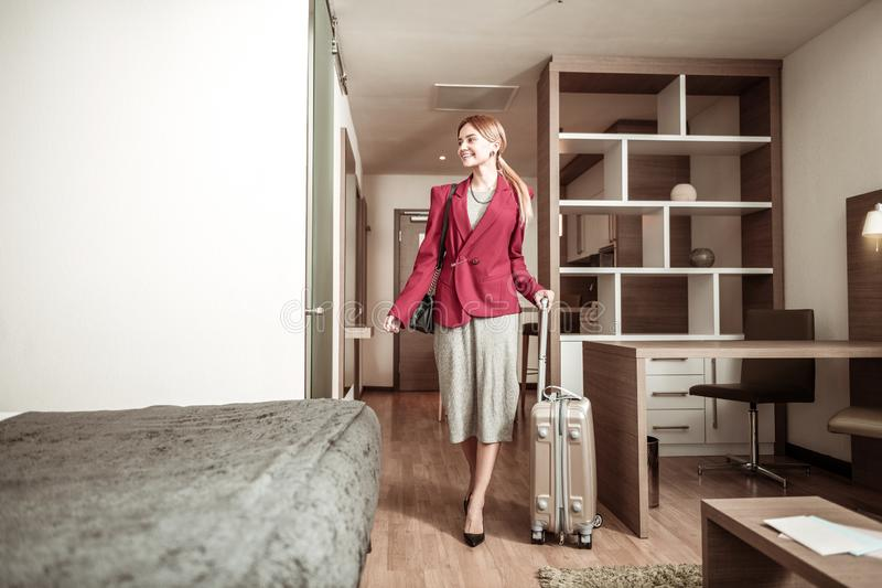 Businesswoman feeling excited coming to hotel with her luggage. Excited businesswoman. Beaming beautiful businesswoman feeling excited coming to hotel with her royalty free stock image