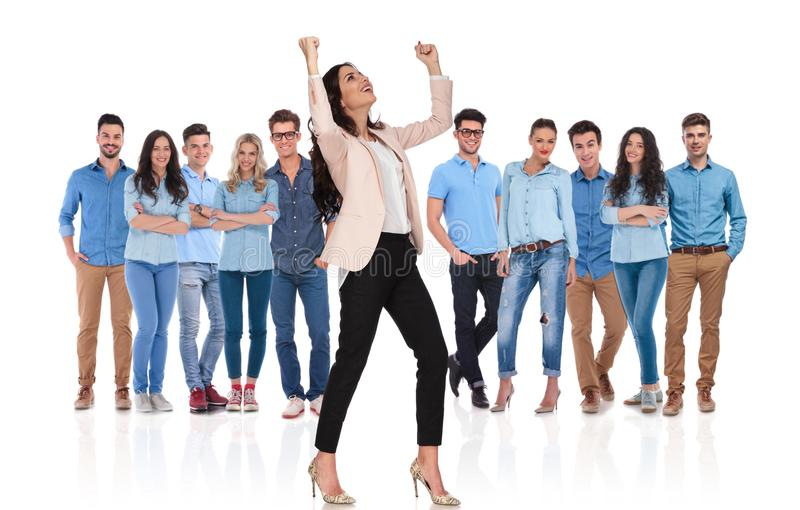 Excited businesswoman celebrating while standing in front of her. Excited businesswoman group leader celebrating with both hands in the air and looking up to royalty free stock images