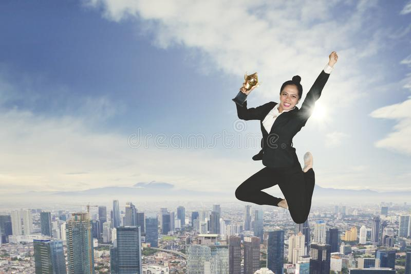 Excited businesswoman dancing with a trophy royalty free stock photo
