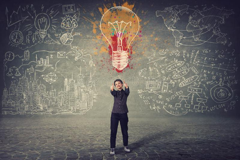 Excited businesswoman, showing thumbs up gesture, stands in front of a wall with drawn colorful light bulb and business sketches. stock photo