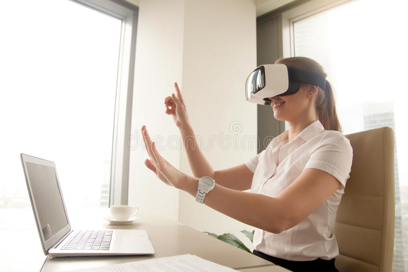 Excited businesswoman in virtual reality glasses trying to touch. Cyber objects, testing VR goggles for business sitting at desk, woman in headset interacting stock photos