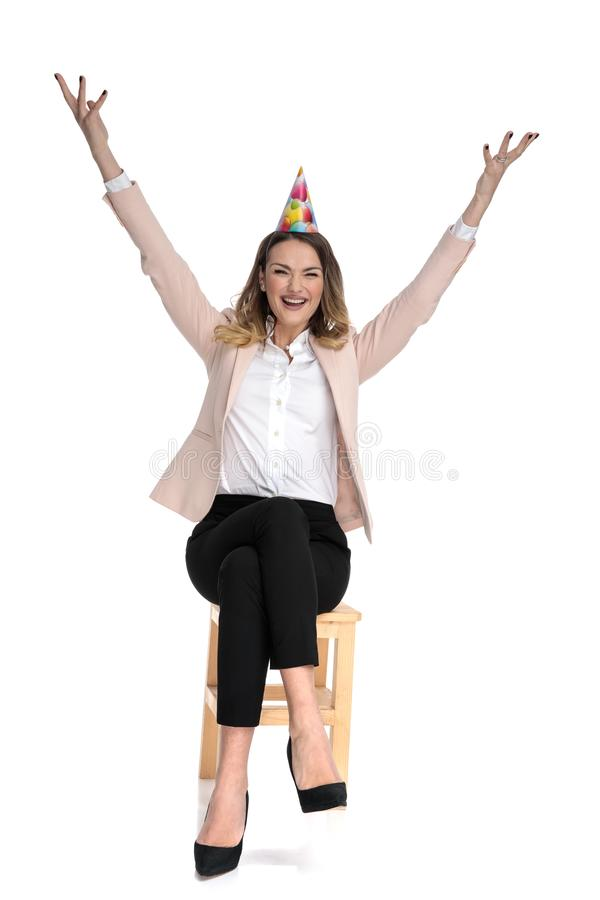 Excited businesswoman wearing birthday hat celebrating. With hands in the air while sitting on wooden chair on white background royalty free stock photos