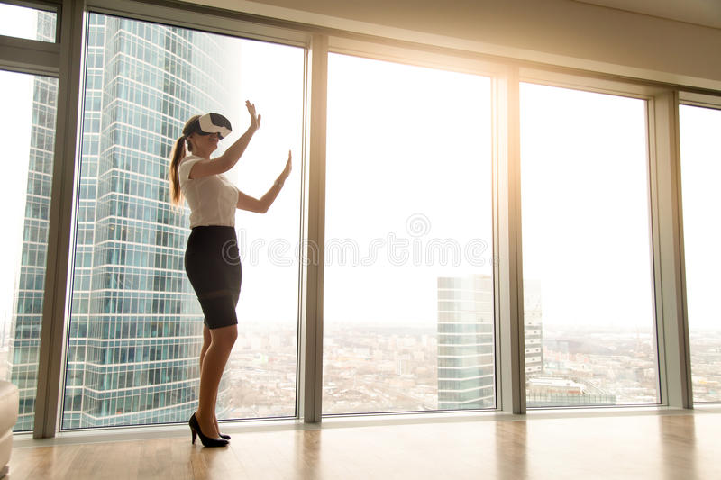 Excited businesswoman wearing headset exploring vr standing near. Excited smiling businesswoman wearing virtual reality glasses, happy woman exploring augmented royalty free stock photos